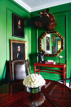 Vibrant green dining room with framed portraits on walls.