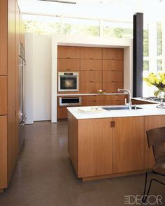 Teak-veneer cabinetry, resin countertops, and polished-concrete floors in this country kitchen.