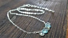 This unique necklace features genuine blue zircon, a rare stone that is not to be confused with cheaper cubic zirconia. It is a beautiful light blue and looks lovely next to the natural labradorite stones. I used tiny Karen Hill Tribe sterling silver beads to complete the center of the necklace. The sterling silver chain is delicate and has a muted finish. This necklace is light, easily wearable and comes with and extender chain. - Materials: Sterling silver chain and components, genuine…