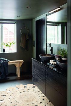 ETTER: Vaskene fra Catania er i svart marmor, og står godt til de mørke veggene. Med innslag av naturelementer fremstår badet som mykt og innbydende. Gjennomgående har Anne Grethe valgt blandebatterier fra Vola. Innredningen er i sortbeiset eik fra JKE. Benk fra Slettvoll. Det meste av dekoren, som for eksempel de tøffe håndklehengerne, har paret funnet hos Egen Stil i Sverige. Catania, Mirror, Bathroom, Furniture, Home Decor, Washroom, Decoration Home, Room Decor, Mirrors