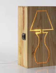 "This neat bed-sider conceals a bulb behind the laser-cut pattern of a ""retro"" lamp punched through its foot-high pine box Articles En Bois, Luminaria Diy, Luminaire Original, Diy Luminaire, Retro Lamp, Wooden Lamp, Lampshades, Wood Design, Lamp Light"