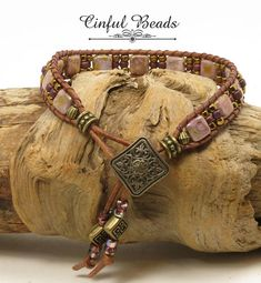 This single wrap leather bracelet uses Czechmate Tile beads in opaque gold/smoky topaz which are a pale purple with splashes of bronze. The tiles are separated with Japanese seed beads. Theyve all been hand stitched to 1.5mm natural brown leather cord thats extremely supple. The