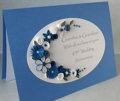 Quilled 65th sapphire wedding anniversary card, handmade, paper quilling. A beautiful quilled anniversary card perfect for celebrating a special 65th anniversary. A sapphire blue background card featuring a die cut oval which has been decorated with an assortment of blue and white