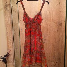 Boho Chic Free People Orange Paisley Print Dress Free People Boho Chic Orange & Pink Paisley Print Dress. Constructed from silk, this dress features a V-neck, a sleeveless design, lace trim, an elastic smock on the waistline, gathering along the hem, orange back button closures, fully lined. Free People Dresses
