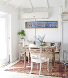 A salmon-hued table used as a desk and an old church pew outfitted with feather-down pillows adorn the office of this tiny Florida cottage.