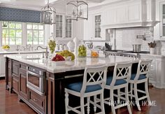 The open kitchen features a stately island topped with Calacatta marble. Bar stools painted white and covered in indigo-blue fabric from Sunbrella are extra roomy and comfortable.
