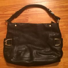 Cole Haan Black Leather Gorgeous Purse This Cole Haan purse has really awesome side pockets with brushed gold looking buckles.  On the inside is a zipper on one side and two pockets on the other side – perfect for holding a cell phone. This purse is a perfect size shoulder bag. Cole Haan Bags