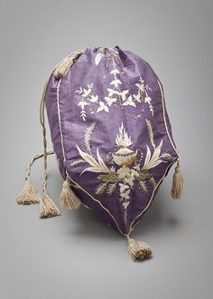 A woman's reticule which was made to carry items. This reticule was made of silk and decorated with embroidery and tassels.