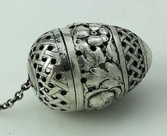 German Pseudo Marked Pull Apart Silver Tea Ball    A German egg shaped tea ball marked on the inside lip and pierced with flowers and lattice work. The tea ball pulls apart and the lid is removed by pulling over the chain. 2 inches tall. Circa 1910