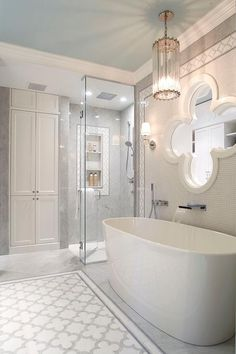 Oversized white trimmed quatrefoil mirror stands out over an oval freestanding bathtub with a waterfall tub filler.