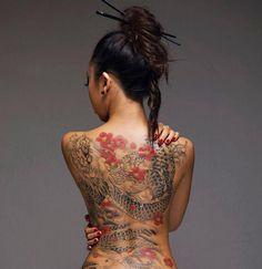 japanische tattoos, frau mit hochgesteckten haaren und großer tätowierung am rücken