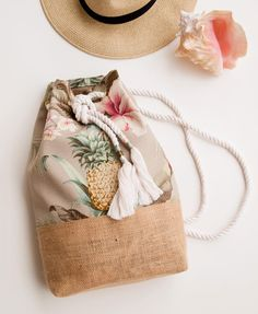Tropical floral pineapple and jute burlap back pack duffle bag a tropical floral print of happy pineapples and soft pink hibiscus flowers covers this fun beach ready backpack the colors in this print are light and lovely pale khaki baby blue blush pink if Diy Sac, Fabric Bags, Summer Bags, Handmade Bags, Fashion Bags, Purses And Bags, Burlap, Pouch, Reusable Tote Bags