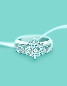 unique Tiffany's round shaped wedding engagement ring with a shared-setting diamond band