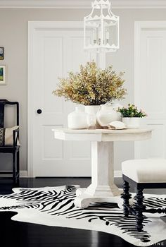 White and bright entryway with table in center and lantern as chandelier