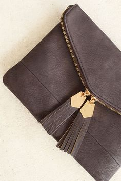 Clutches are a must and this chocolate colored beauty is a definite. This faux leather number adorned by gold accents and two tassels will quickly become a favorite in your fall wardrobe. This warm co