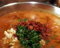 Manhattan Clam Chowder ~4 slices bacon 2 tablespoons olive oil 3 cloves garlic 1 medium onion 2 medium carrots 2 dried bay leaves 2 teaspoons dried oregano 1/2 teaspoon crushed red pepper flakes 6 Yukon Gold potatoes 4 cups clam juice 2 cans chopped clams 1 28oz can whole tomatoes 1/4 cup chopped fresh parsley dash salt and pepper