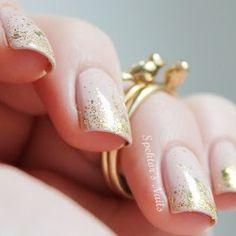 Elegantes uñas decoradas en color beige y adornadas con brillos dorados.
