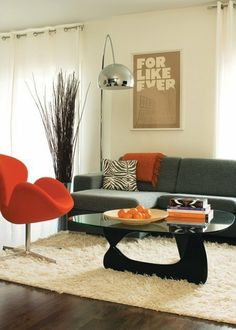 A bowl of oranges, a striking Jacobsen Swan chair and a tangerine-coloured throw add vibrancy to an otherwise neutral colour palette of cream, brown and grey.