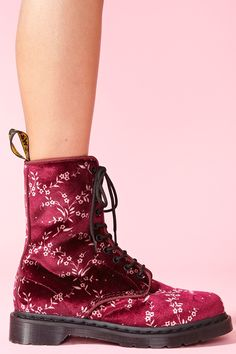The iconic lace-up combat boot in cherry red velvet featuring a cream floral print and logo bootstrap at back. Gum rubber sole, low stacked heel. Fully lined. Looks perfect paired with a lace dress and cross pendant! By Dr. Martens.