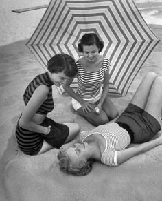 Models on beach wearing latest beach fashions. May, 1950
