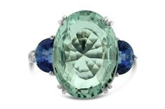 <b>14kt White Gold, Aquamarine, Diamond and Tanzanite Lady's Ring</b> <br /> Central, oval, faceted aquamarine measuring approx. L.17.55 x W.12.99 x D.9.01mm, weighing approx. 11.43-12.08ct.  Accented by two (2) half moon, faceted, tanzanite, measuring approx. L.7.25 x W.4.5mm each.  Top sides of shank accented by approx. 12 round brilliant cut diamonds at approx. .02ct each, totaling approx. .24ct.  Not stamped or signed.  Approx. 7.82 grams total.
