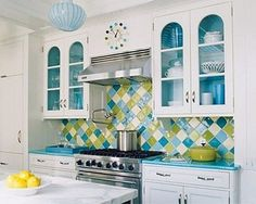 Turquoise Harlequin Kitchen.  Multi-color tile backsplash. Upper cabinets have painted interiors - accent color.  Atticmag.com