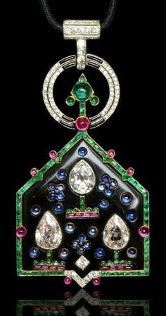 A highly important Art Deco pendant of Mughal inspiration, designed by Charles Jacqueau for Cartier Paris, circa 1921. The pentagonal onyx plaque set with three stylised topiary motifs, 2 with a large pink tinted pear-shape diamonds and 1 with a large blue tinted pear-shape diamond amongst sapphire cabochons to a border of calibré-cut emeralds punctuated with rubies suspended from an emerald-set arrow within two concentric circles set with bands of diamonds and onyx.