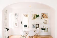 light filled dining room :: scandinavian chairs, art gallery on shelves