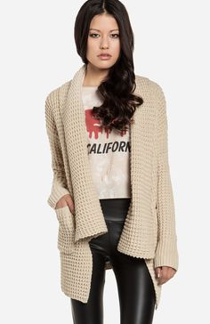 Cozy, oversized cardigan featuring a draped open design, two patch pockets on hips, shawl collar, ribbed cuffs and back hem, and split side seams.
