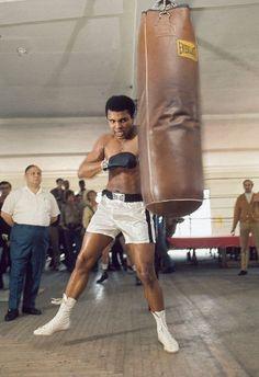 Heavyweight boxing champion Muhammad Ali demonstrates his strength on the heavy bag (Moneta Sleet, Jr./Ebony Collection)