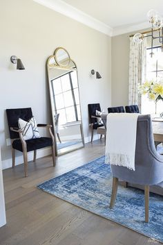tip to make your home feel cozy and inviting with curtains, flowers and art blue vintage inspired rug black tufted dining chairs kravet riad custom curtains sw mindful gray-2