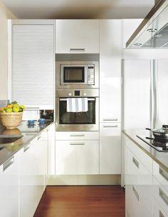 Frigorifico-gavetero-hornos Amplia capacidad En una de las paredes de la cocina se instaló un mueble-columa, de suelo a techo, hecho a medida, que alberga, de izquierda a derecha, el frigorífico, un gavetero extraíble, los hornos y un módulo con una puerta de persiana.