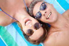 Casal feliz com óculos de sol na praia Foto gratuita