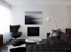 Fantastic modern living room design with navy blue linen tufted sofa with chaise lounge, CB2 Smart Round Marble Top Coffee Table, white & black cowhide rug, Marimekko Tuuli fabric pillows, blue abstract art, modern floor lamp, built-in fireplace and Restoration Hardware 1950s Leather Copenhagen Chair.