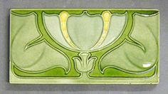 """Maw and Co relief moulded dust pressed tile with a stylized floral design in Art Nouveau style, grey, green and yellow glazes, 6"""" x 3"""", c1910."""