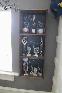 DIY trophy case with chalkboard backing! You can write messages or makes notes for each trophy.