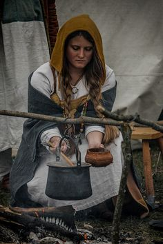 Female viking reenactor, cooking over open fire.