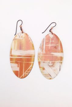 Resin + Copper Earrings by Lauren Collignon for Flaming Lotus Jewelry.  These earrings feature an orange paper print, covered in resin and mounted on copper backs with copper ear wires. Handmade in Louisiana. $58.
