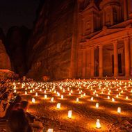 """The Al Khazneh or Treasury illuminated by candle-lights during the """"Petra by Night"""" show. Petra is a UNESCO World Heritage Site and is famous for its many rock-cut monuments by the Nabateans.  Petra is """"touristy"""" but still well worth the visit.  The walk to the Treasury takes a good 20 to 30 minutes from the main gate; I'd recommend bringing a flashlight for additional lighting along the pathway.  (This image was featured in Nat Geo Travel Your Shot: Night Pictures.)"""