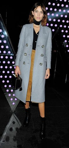 Alexa Chung wears a gray trench with a black top, a midi-skirt and a black choker.