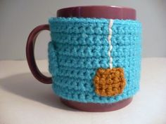 """Crochet Pattern: """"Cup of Tea"""" Coffee Mug Cozy with Non-Slip Backing.  This week's challenge for Iron Craft was to make a coffee cozy.  What a perfect crochet project!  I made mine to look like a cup of tea, with an applique-and-embroidery tag and string on the side.  I also gave it a non-slip backing, so it won't slide around precariously on my mug while keeping it warm."""