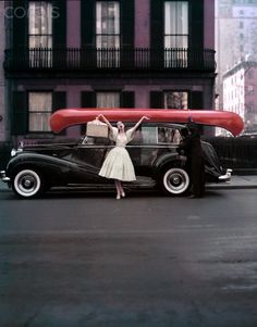 Fashion model Barbara Mullen poses arms wide and mouth open in front of a model dressed as a chauffer tying a red canoe onto a black Rolls-Royce in front of a purple building.  1950s  William Helburn