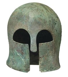 A GREEK BRONZE HELMET OF CORINTHIAN TYPE   ARCHAIC PERIOD, CIRCA EARLY 6TH CENTURY B.C.   Hammered from a single heavy sheet, of domed form, the neck-guard flaring, the elongated almond-shaped eye holes bevelled at the edges, bordered along the perimeter with small perforations