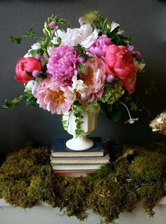 Pink, purple, coral, white peonies with viburnum, ivy, gomphrena, clematis, freesia in footed vase. Beautiful, but if it weren't for the books, the flowers would overwhelm that vase!
