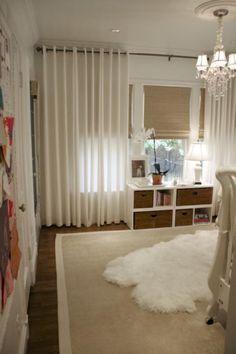 Chic white gender neutral nursery design with West Elm Linen Cotton Grommet Window Panels - White, bamboo roman shades, sheepskin rug and crystal chandelier.