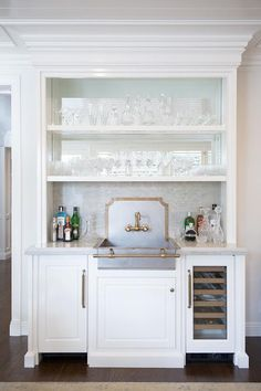 Chic wet bar boasts white cabinets fitted with a metal apron sink and backsplash accented with brass trim and a brass vintage faucet placed under shelves with a mirrored backsplash.