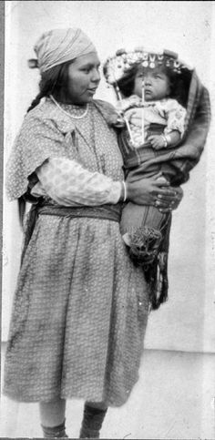 Colville woman named Katie Nanpooya George holds baby in cradleboard, Washington. Northwest Museum of Arts and Culture, American Indians of the Pacific Northwest Collection