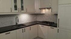 White mosaic tiles and steel Grey granite counter