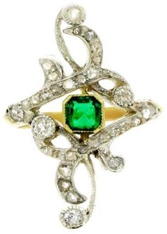 Emerald and diamond Art Nouveau ring, circa 1895. Openworked ring set to centre with an octagonal emerald in a yellow gold, millegrained, rub over collet with an approximate weight of 0.50ct. Thirty-three round old cut diamonds set to freeform carved silver topped mount, with an approximate total weight of 0.80ct. Mounted and set in silver and yellow gold. Berganza.