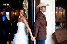 A country groom with his darling bride at the southern wedding venue--THE SPRINGS.  Love her gorgeous wedding dress and the groom's cowboy hat!  Plus love the wedding photo of holding hands on either side of the door.